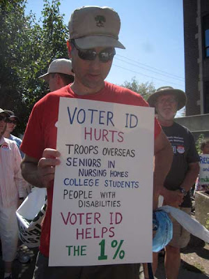 Man holding sign with list of people hurt by requiring voter ID, ending with Helps the 1%