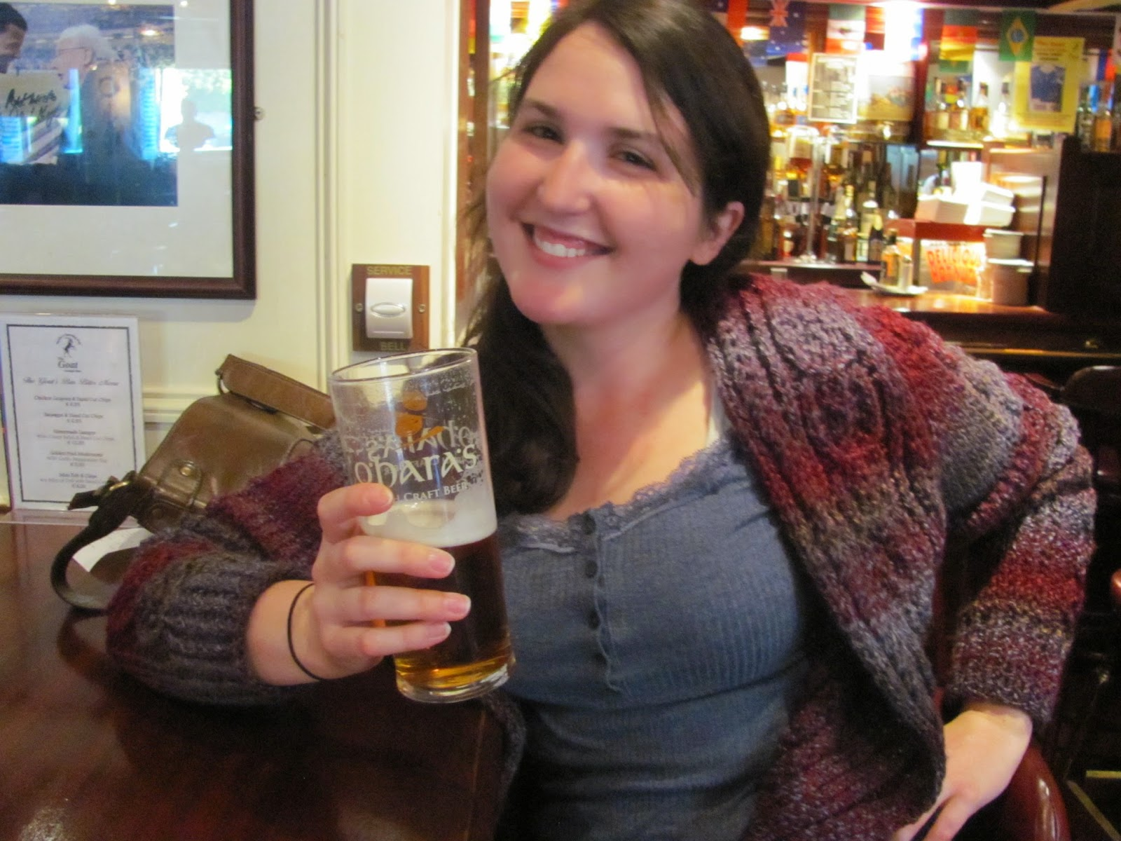 Sara modelling the front of her sweater in a pub