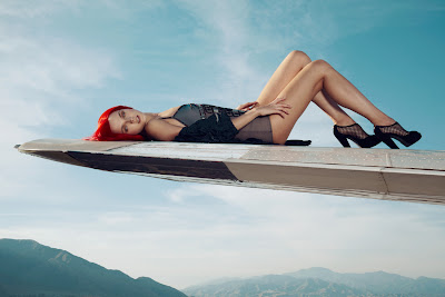 top fashion photographers nyc, woman laying on airplane wing, airport