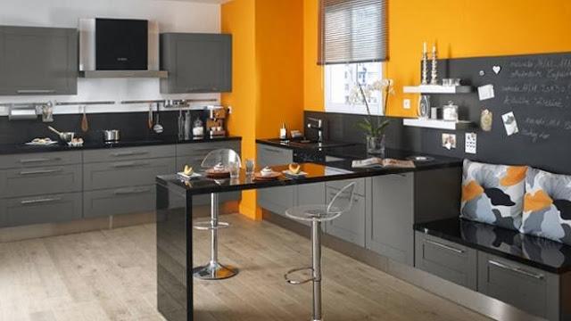 Cuisine contemporaine et chaleureuse. Cuisine équipée gris anthracite sur mur orange, façade à cadre en bois massif laqué et plan de travail noir brillant.