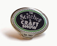 Stitches and Craft Fair enamel badge displays the event logo.