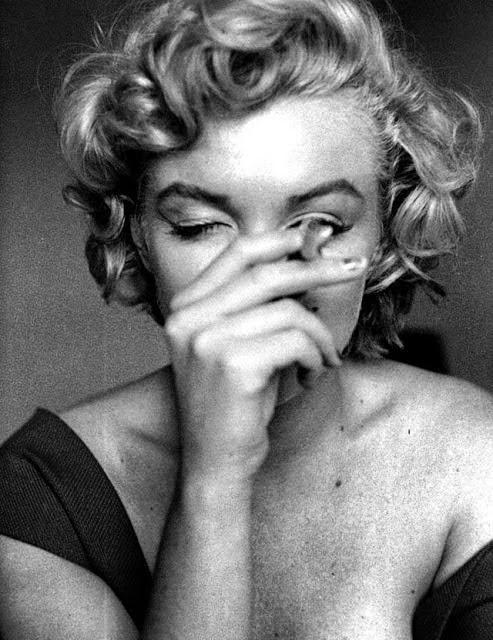 photgraphie de marilyn monroe portrait faisant un clin d'oeil et fumant une cigarette cheveux décoloré blonde platine sourire