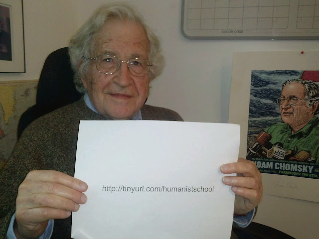 Noam Chomsky holding up a sign saying http://tinyurl.com/humanistschool