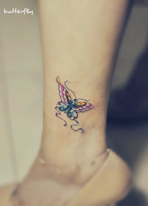 a pink and blue butterfly tattoo on the leg