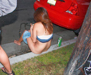 funny picture: drunk girl taking a piss while sitting on the sidewalk