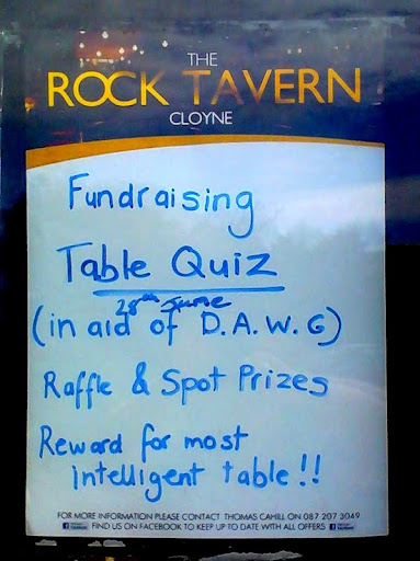 blue text on white background - The Rock Tavern, Cloyne, Co Cork, Ireland - Fundraising Table Quiz in aid of DAWG - 28 June - raffle and spot prizes - rewards for the most intelligent table.