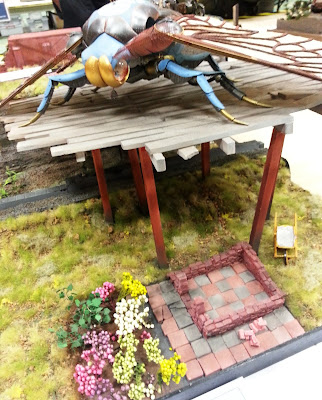 A diorama of a giant insect above a patio and garden bed at a scale model exhibition.