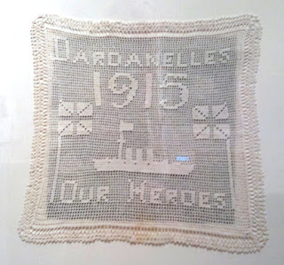 """White filet crochet square mat with the words """"Dardanelles 1915 Our Heroes"""" and images of a ship and union jack flags."""