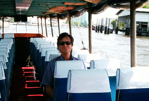 Man sitting alone in an empty boat with lots of seats