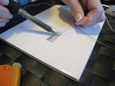 Woman adding flux to length of wire on a run of copper tape.