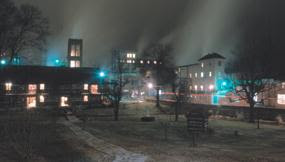 a spooky view of the distillery buildings a night with lights showing through fog