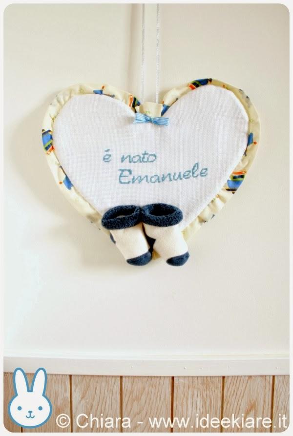 Fiocco nascita a forma di cuore con scritta ricamata a punto croce e calzine mignon