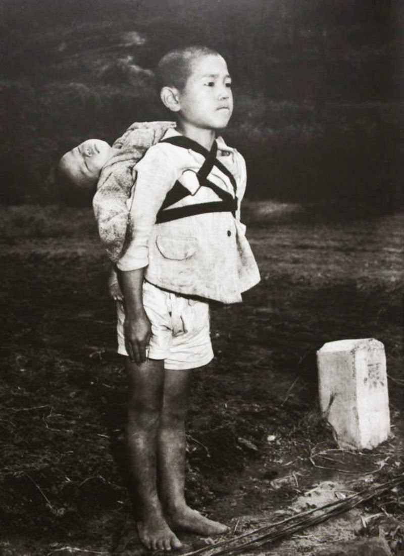 A+Japanese+boy+standing+at+attention+after+having+brought+his+dead+younger+brother+to+a+cremation+pyre,+1945.jpg