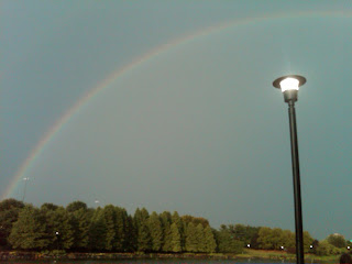 rainbow over a lake and lamp post