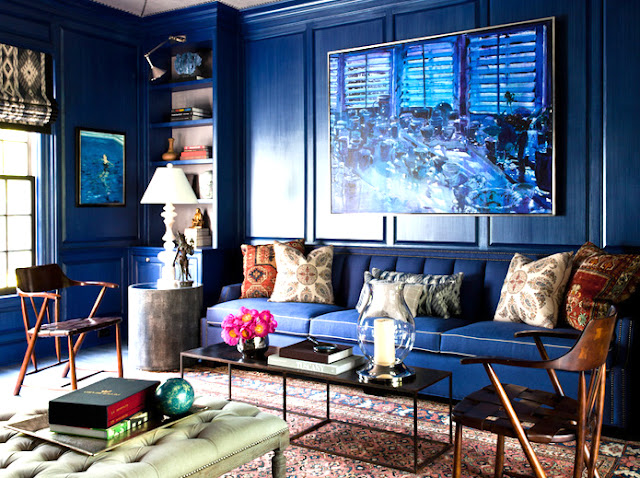 Library with blue walls with a large blue painting on the wall, a blue couch with patterned pillows and a Moroccan rug with blue accents