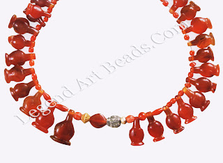 This necklace consists of sixty-nine carnelian pomegranate-shaped and round beads, two gold beads, and one scarab.