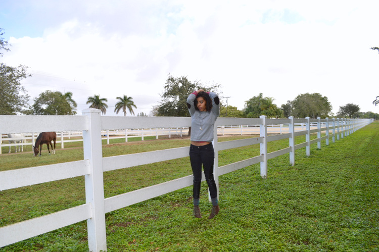 Fashion Blogger Anais Alexandre of Down to Stars in a Forever 21 elbow patch sweater, plaid buttondown , Tripp NYC leather patch pants and Forever 21 argyle socks and brown combat boots near a horse stable
