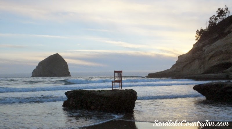 Red chair sitting on rock in ocean overlooking Haystack Rock, Cape Kiwanda