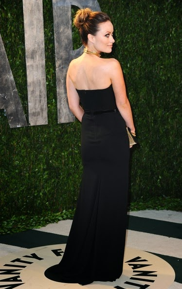 Olivia Wilde sported a sleek ballerina bun and kohl-rimmed eyes with her black strapless silk georgette evening gown accentuated with a sequin-embroidered black velvet belt and paired with a gold choker, a couple of gold bangles and a matching gold clutch at the 2012 Vanity Fair Oscar Party hosted by Graydon Carter at Sunset Tower on February 26, 2012 in West Hollywood, California.