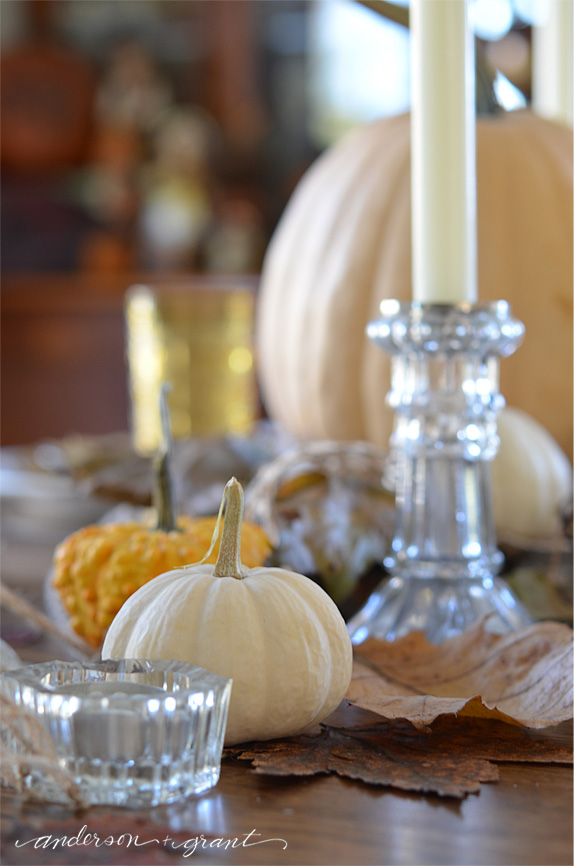 Collection of glass candlesticks and pumpkins in Thanksgiving centerpiece | www.andersonandgrant.com