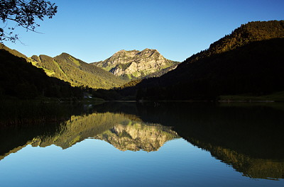 View of Vallon lake in Bellevaux with Roc d'Enfer mountain reflected in the water at dusk.