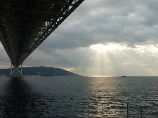 Underside of the Akashi Kaikyo Bridge in the afternoon. The bridge streches into the distance where Awaji Island is visible. There are a few large ships in the ocean and the afternoon shin is shining through some clouds and lighting up the ocean