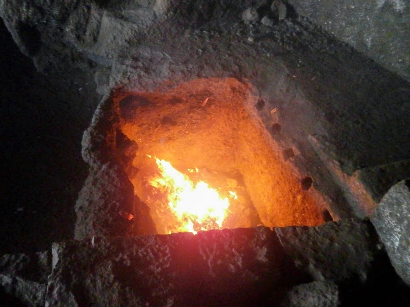 Burning waste in a pit inside the cave on Alang