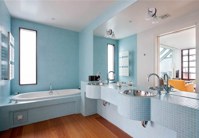 bathroom with wood floor but the walls, appliances (step in tub, sink, counter) are covered in light blue tiles