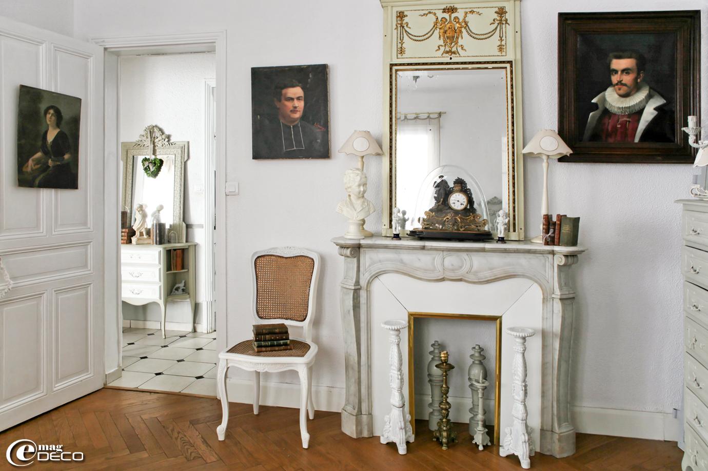 Posés sur une cheminée en marbre d'époque, un trumeau chiné à la brocante de Codognan et une pendule de style Napoléon III sous un globe en verre chinée à l'Hôtel Drouot à Paris