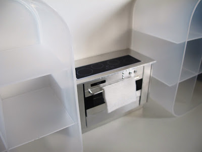 Modern dolls' house miniature metal stove between two white perspex shelving unit
