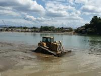 浅くなった川底のショベルカーで砂利を掘削していた。
