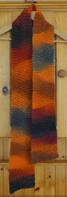 'Vesuvius' slip stitch scarf on a coathanger hanging on a pine dresser.