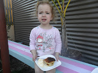 Young girl enjoying the pikelets she made.