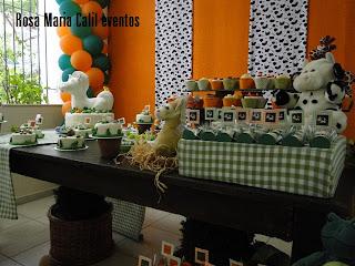 mesa madeira, painel de tecido laranja e branca e preta, bichos pelucia, toppers, caminha mesa e caixas xadrez verde