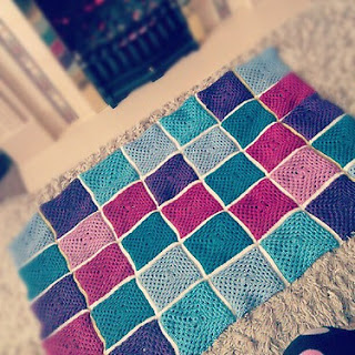 a crocheted blanket handmade with granny squares