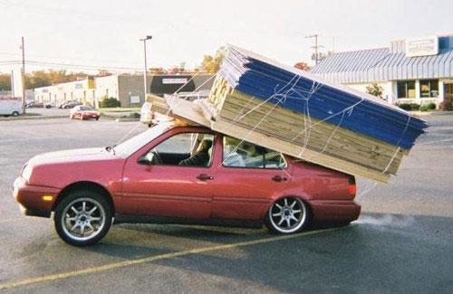 Une voiture de bricoleur surchargée sur le parking d'un magasin de bricolage.