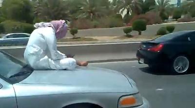 Homem ao telemóvel e em cima do capot dum carro a 90 Km/h