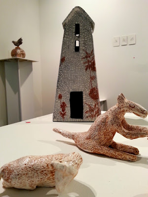 Clay house on display in a gallery. In front of it is a clay kangaroo and sheep.