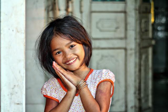 Photographie du visage d'une enfant jouant dans les allées du marché de Borey Santheapeap 2 dans la banlieue proche de la capitale Phnom Penh