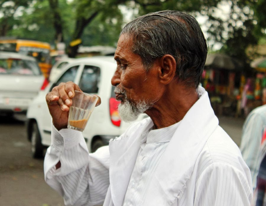 Man drinking chai or tea in a glass