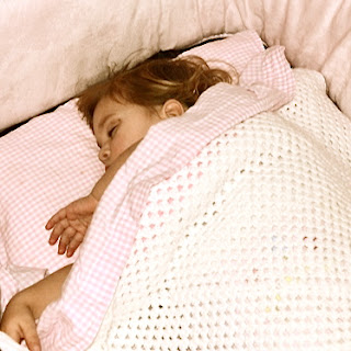 Niñas duermen con la manta de abuela hecha a ganchillo