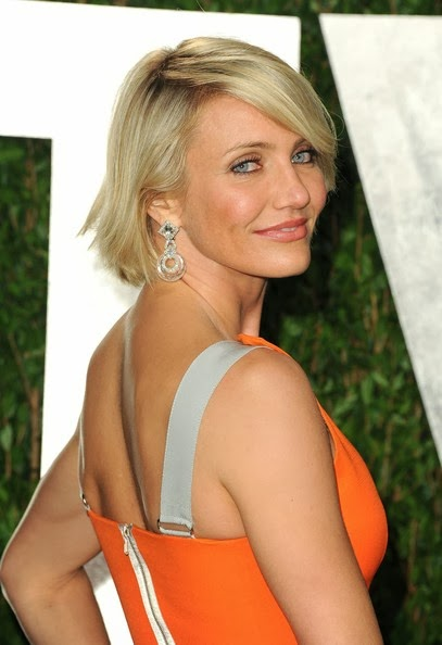"Cameron Diaz looked stunning in a figure-hugging vibrant orange gown from Victoria Beckham's Spring 2012 collection at the 2012 Vanity Fair Oscar Party hosted by Graydon Carter at Sunset Tower on February 26, 2012 in West Hollywood, California. The ""Bad Teacher"" star paired her bold tangerine-colored dress with David Webb jewels, including a pair of oversized diamond chandelier earrings and a thick bangle, and a matching minaudière."