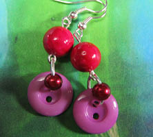 Long dangling earrings in pink have layered fashion buttons and small beads hanging from dark pink river stones