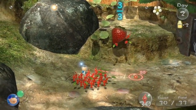 Red Pikmin in the Wii U game Pikmin 3 standing next to a strawberry.