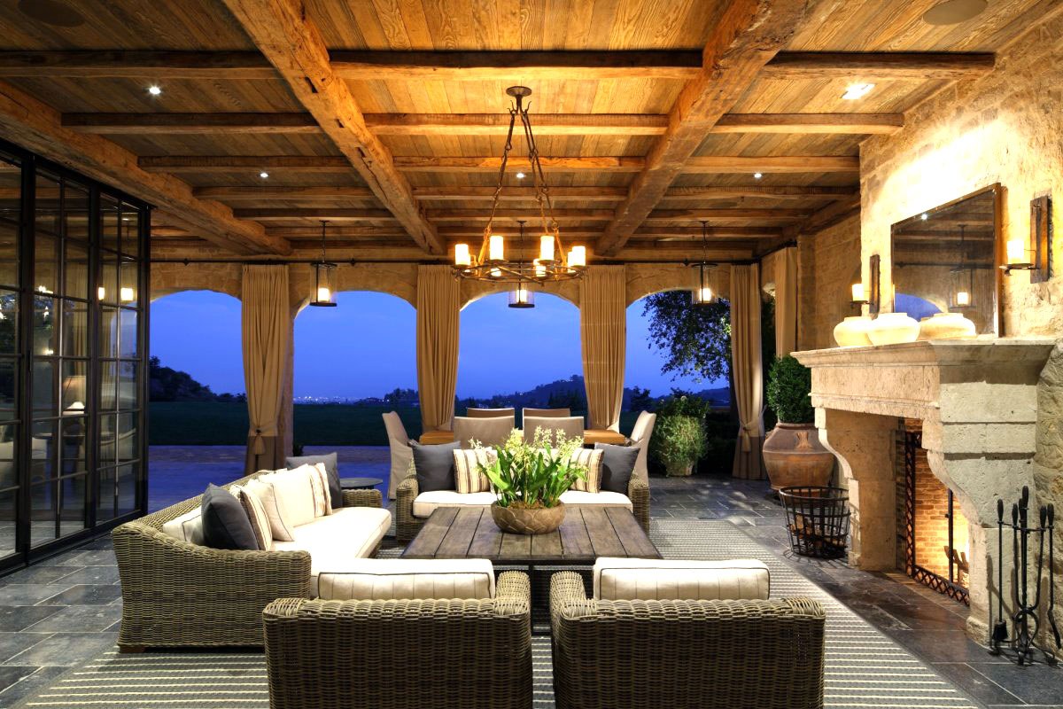 Outdoor sitting area with woven furniture, fireplace and chandelier