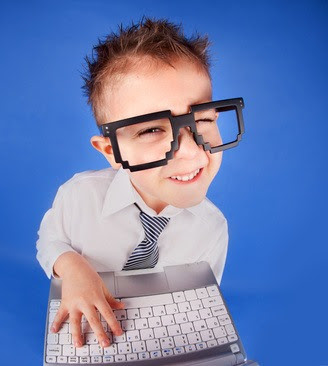 Little boy wearing glasses and making a silly face while holding a computer