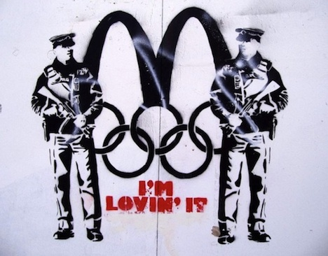 "Street Art of two police officers guarding McDonalds Symbol over the Olympic rings and the words ""I'm lovin' it"""