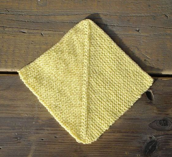 yellow knitted square on wooden background. Square is knitted in garter stitch, and the stocking stitch rib running from point to point is less prominent on one side.