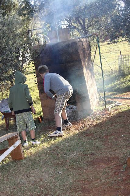 Die seuns maak vuur in die donkie vir warm water om in te bad