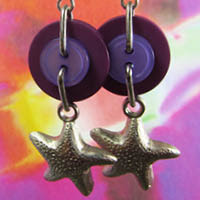 Lucky charm earrings have silver starfish charms hanging from layered purple buttons